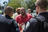 Carlos Valnera of Black Lives Matter Alliance of Broward talks to the police about safety measures during a protest in front of Hollywood's City Hall where people demanded the removal by the city commission of street signs named after confederate generals and KKK wizards on Wednesday August 30, 2017<br /> <br /> photo by Samuel Navarro