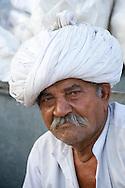 An old man wearing a large white turban in the Sardar Market in Jodhpur, Rajasthan, India
