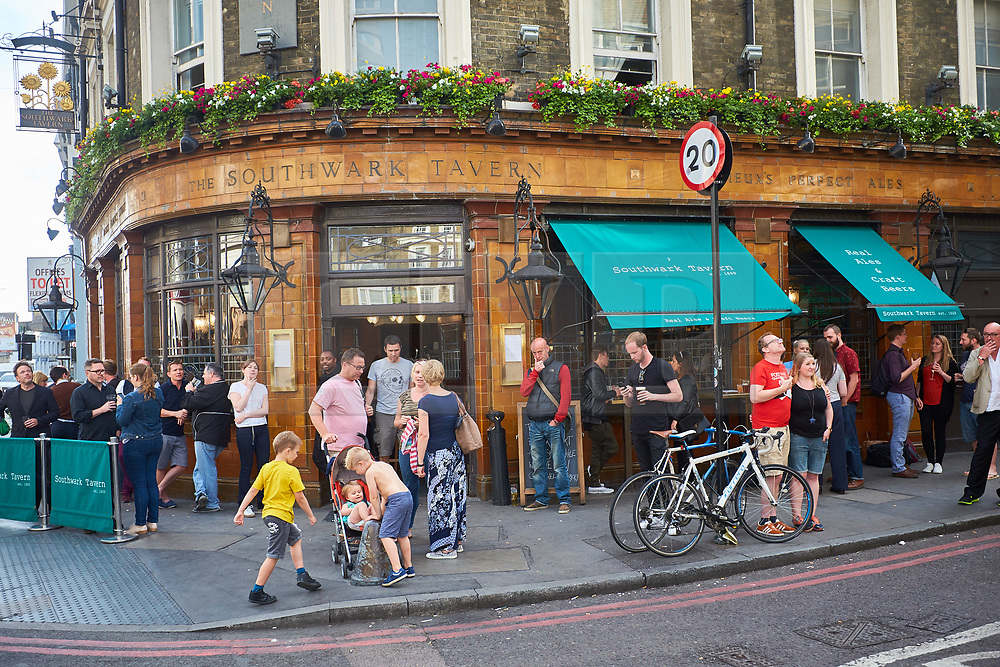 © Licensed to London News Pictures. 11/06/2017. LONDON, UK.  Drinkers outside the Southwark Tavern pub near Borough Market. The market remain has remained closed since a terror attack a week ago killed eight people but is expected to begin reopening tomorrow (Monday).  Photo credit: Cliff Hide/LNP