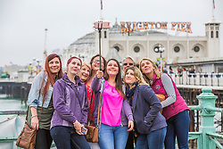 © Licensed to London News Pictures. 12/05/2018. Brighton, UK. A group of friends take a selfie in front of the Brighton Palace Pier in Brighton and Hove as colder and grey weather is hitting the seaside resort. Photo credit: Hugo Michiels/LNP