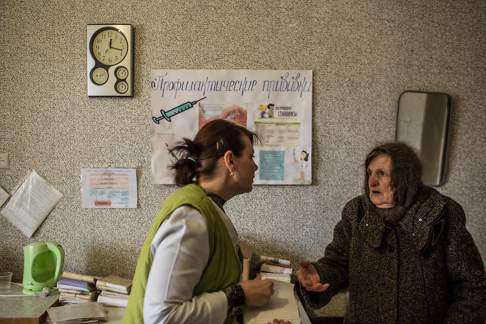 ZIMOGORYE, UKRAINE - MARCH 15, 2015: Yelena Beybudova, a nurse, consults with a patient at the Zimogoryivskaya Ambulatory in Zimogorye, Ukraine. CREDIT: Brendan Hoffman for The New York Times