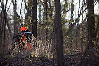 DEER HUNTER WEARING REALTREE AP CAMOUFLAGE AND BLAZE ORANGE WHILE SHOOTING A THOMPSON CENTER OMEGA MUZZLELOADER