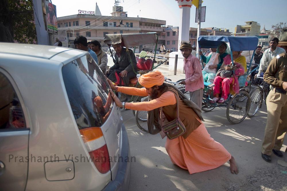 A holy man pushes his broken down car a a traffic junction during the Maha Kumbh ceremony in Haridwar, February 11, 2010.  Photographer:Prashanth Vishwanathan