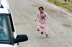 A Young Iraqi girl asking for water runs towards a British Army patrol of Royal Dragoon Guards travelling in civilian vehicles as it passes through Umm Qasr area Southern Iraq near the Kuwait border, while on Op-Telic in March 2005