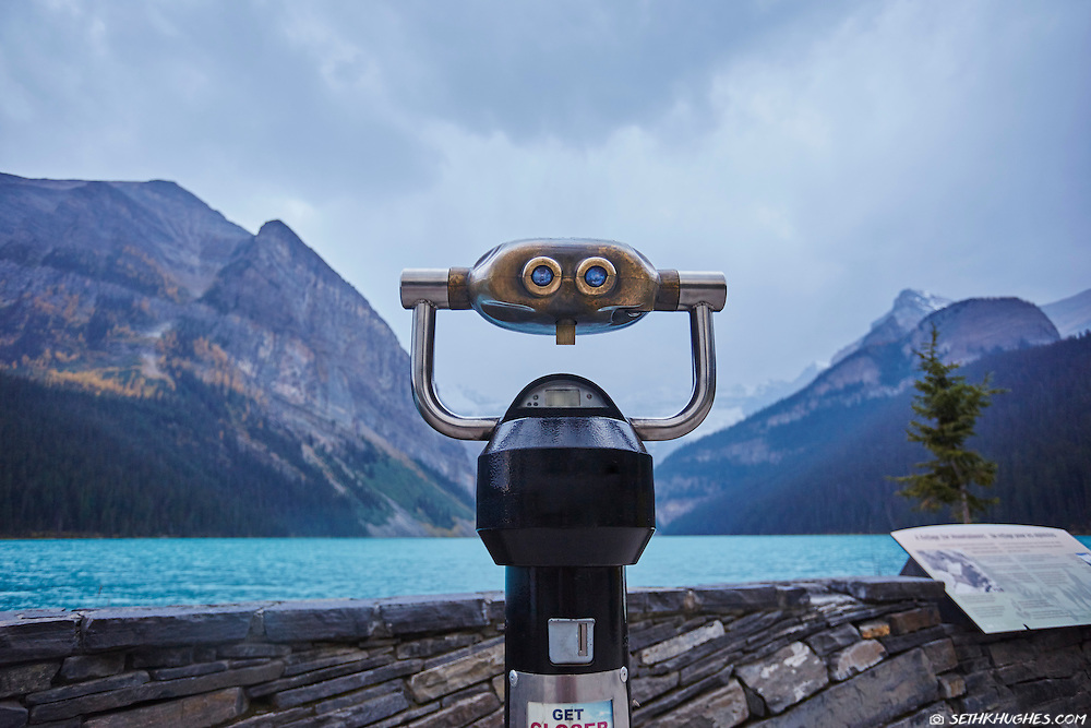 A viewpoint with binoculars looking across Lake Louise towards a storm as it approaches from the mountains.