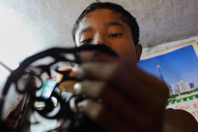 Young worker in a rickshaw workshop in Old Dhaka cutting in plastic pieces the patterns that will be fixed on the rickshaw parts and body. (Dhaka, Bangladesh)
