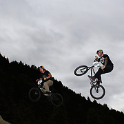 Mike Hucker Clark, (left) and Brandon Docsh in action during the 'Red Bull Roast It' BMX competition with riders from around the globe competing at the Gorge Road Jump Park, Queenstown, South Island, New Zealand. 18th February 2012. Photo Tim Clayton