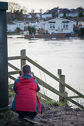 © Licensed to London News Pictures. 03/01/2014. Christchurch, Dorset, UK. A man taking a photo of the houses at Iford Bridge Home Park along the River Stour in Christchurch, Dorset, UK on a day that will bring the risk of flooding to much of the south west of England & Wales. A severe weather warning has been issued by the Environment Agency for the area. Photo credit : Rob Arnold/LNP