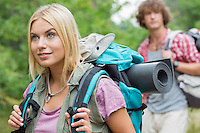 Beautiful female backpacker looking away with man in background at forest
