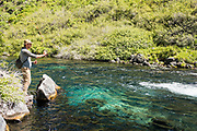 Fly fisherman casting into clear blue water below the falls in the natural spring water at Box Canyon State Park, Wendell, Idaho.