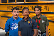 Students pose for a photograph with a bus at Clifton Middle School, June 9, 2015.