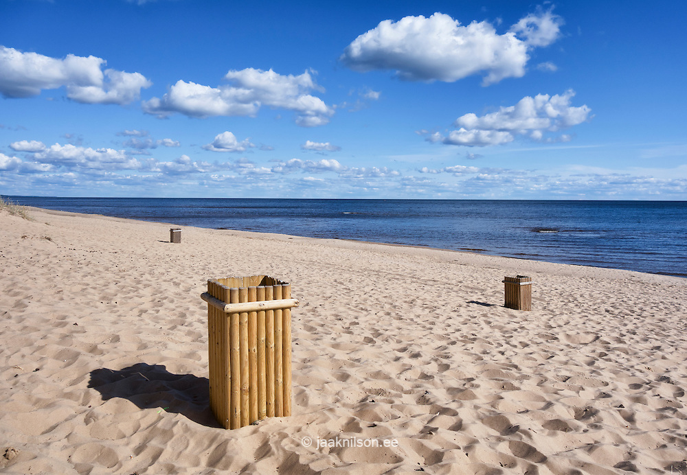 Wooden eco garbage can on empty sandy Kauksi beach at Lake Peipsi in Estonia. Water, clouds and trash-can.
