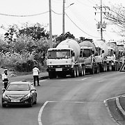 Construction trucks waiting for the police to clear the gate