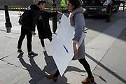 A woman carries a white board with blue arrows pointing the correct direction, on 21st March 2017, in London, England.