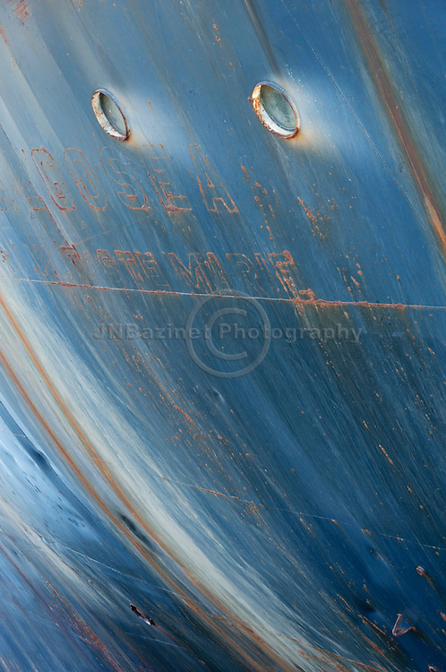 The oxidation process combined with excessive wear produces a creative canvas of rust and blue hues on the side of a ship.