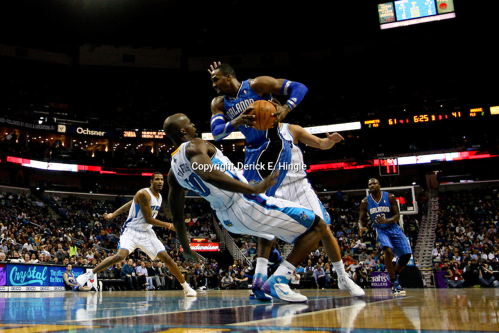 January 27, 2012; New Orleans, LA, USA; Orlando Magic center Dwight Howard (12) draws a foul from New Orleans Hornets center Emeka Okafor (50) during the second half of a game at the New Orleans Arena. The Hornets defeated the Magic 93-67.  Mandatory Credit: Derick E. Hingle-US PRESSWIRE