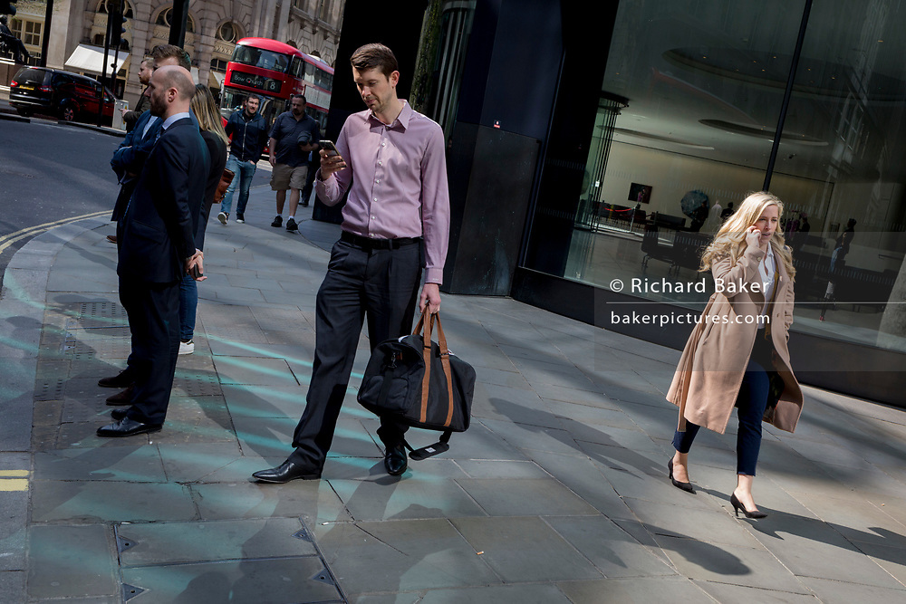 Londoners walk through reflected light while using their phones at lunchtime on Threadneedle Street in the City of London, the capital's financial district also known as the Square Mile, on 6th April 2017, in London, England.