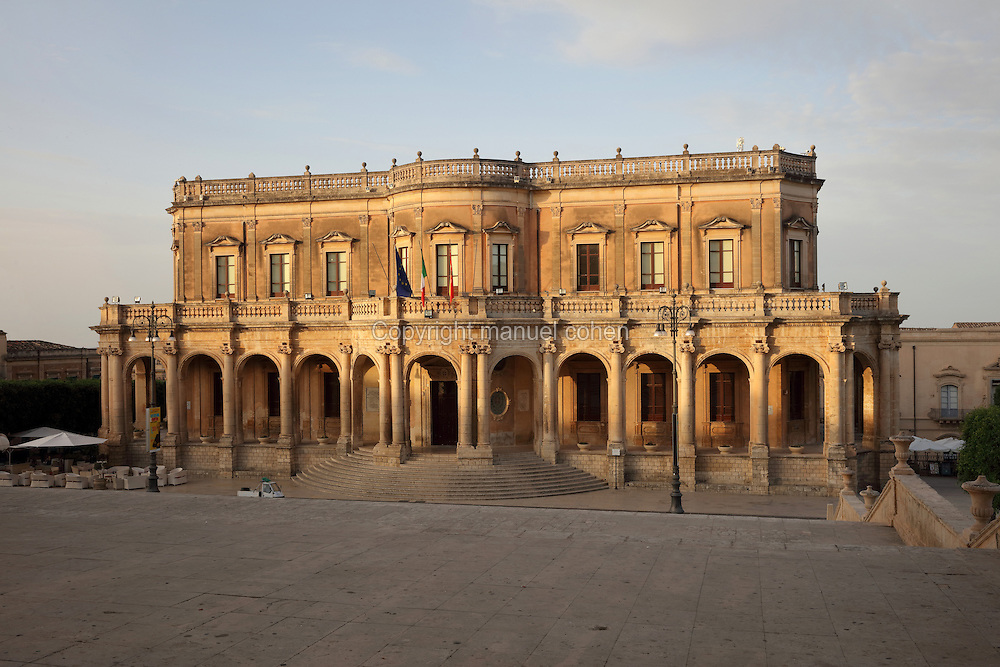 Noto Town Hall, the Palazzo Ducezio, designed by Vincenzo Sinatra in 1746 and completed in 1830, and the second floor was built in the 20th century by Francesco La Grassa, Noto, Syracuse, Sicily, Italy. The convex facade features arches supported by columns with Ionic capitals in the lower section, and 13 windows above. The Palazzo Ducezio is named after Ducezio, King of the Sicilians from 460-450 BC and founder of Noto. Much of Noto was rebuilt after the earthquake of 1693 and the Sicilian Baroque style is therefore prevalent. Noto is listed as a UNESCO World Heritage Site. Picture by Manuel Cohen