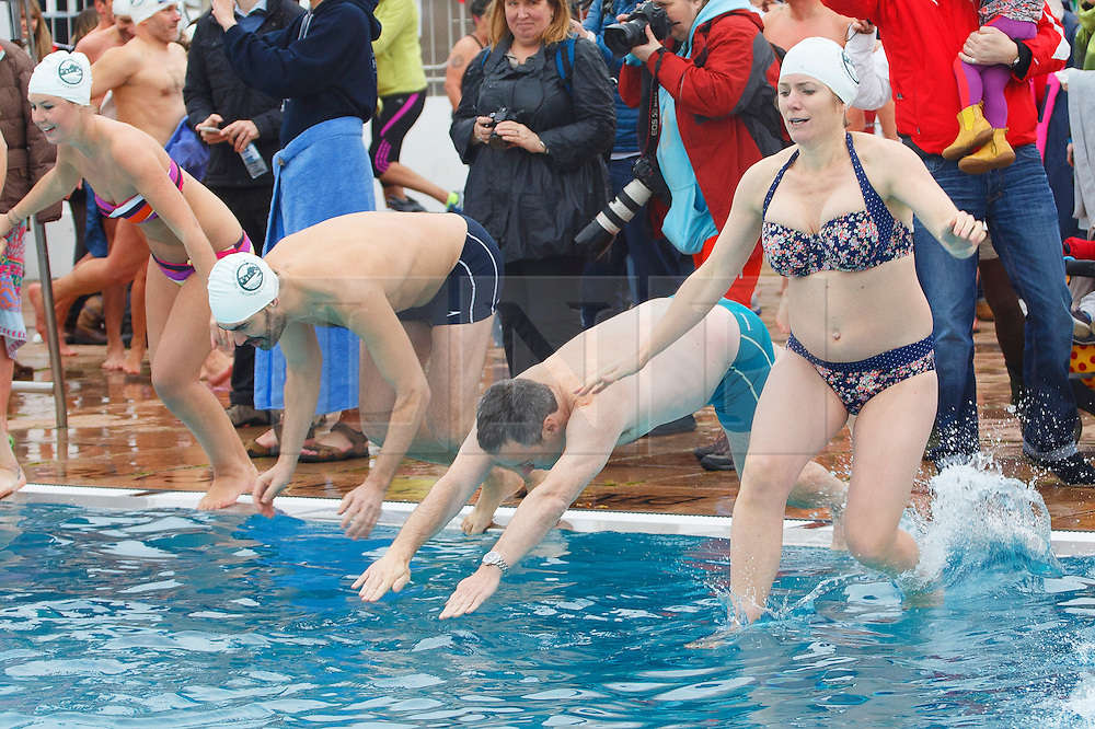 © licensed to London News Pictures. London, UK 07/12/2013. About 400 swimmers plunging into 7C degrees cold Parliament Hill, Lido swimming poll in north London during the December Dip event by Outdoor Swimming Society on Saturday, 7 December 2013. The poll temperature is 7C degrees. Photo credit: Tolga Akmen/LNP