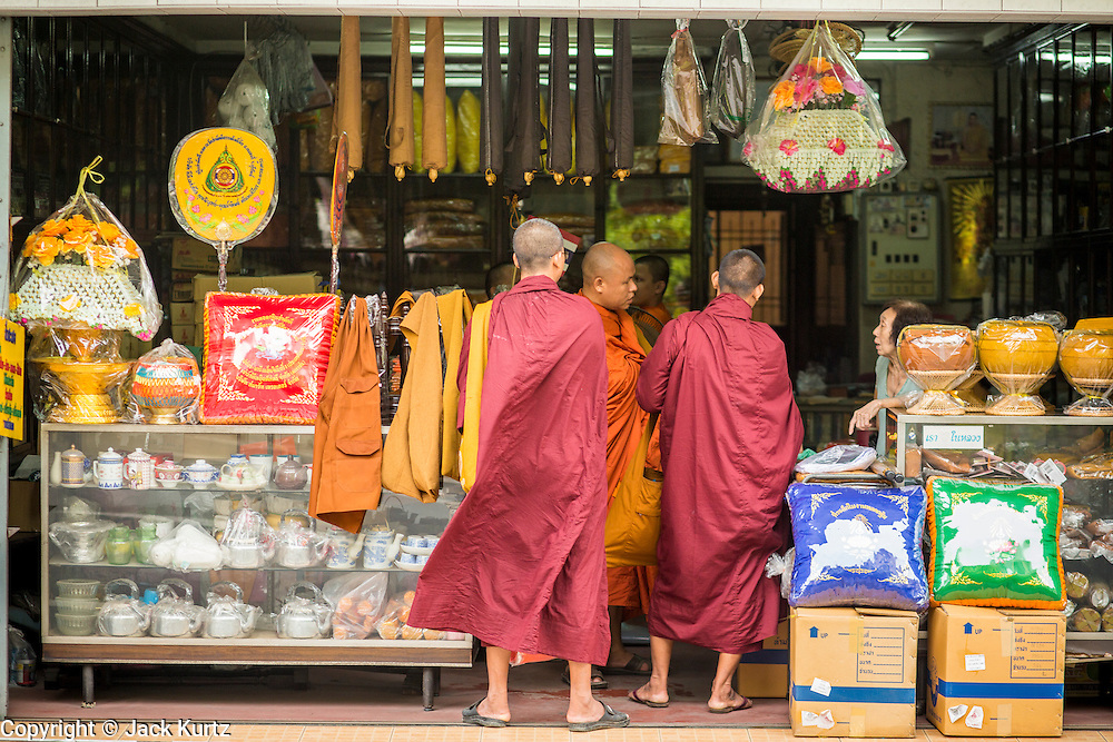 """12 NOVEMBER 2012 - BANGKOK, THAILAND:   Buddhist monks shop in a store that sells Buddhist supplies on Bamrung Muang Street in Bangkok. Thanon Bamrung Muang (Thanon is Thai for Road or Street) is Bangkok's """"Street of Many Buddhas."""" Like many ancient cities, Bangkok was once a city of artisan's neighborhoods and Bamrung Muang Road, near Bangkok's present day city hall, was once the street where all the country's Buddha statues were made. Now they made in factories on the edge of Bangkok, but Bamrung Muang Road is still where the statues are sold. Once an elephant trail, it was one of the first streets paved in Bangkok. It is the largest center of Buddhist supplies in Thailand. Not just statues but also monk's robes, candles, alms bowls, and pre-configured alms baskets are for sale along both sides of the street.    PHOTO BY JACK KURTZ"""