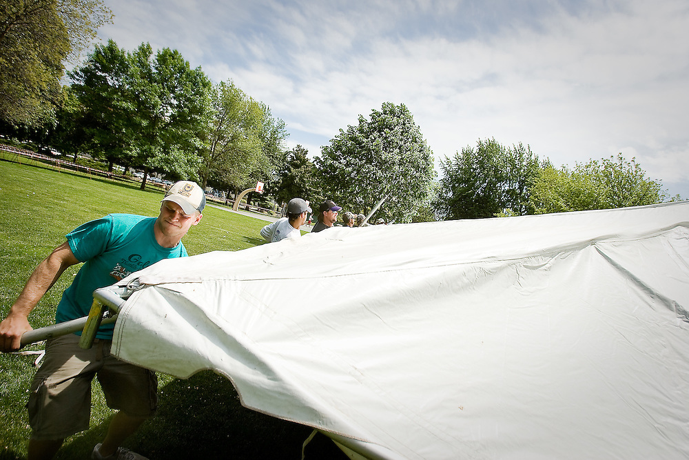 JEROME A. POLLOS/Press..Andrew Eastlich, from White Water, Wisc., helps lift a corner of a tent Tuesday  during the construction of the Ironman Village in City Park.
