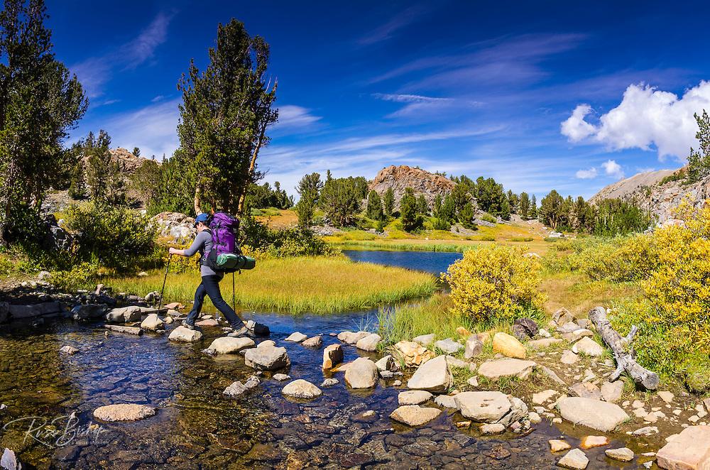 Backpacker crossing a stream on the Bishop Pass Trail, John Muir Wilderness, Sierra Nevada Mountains, California USA