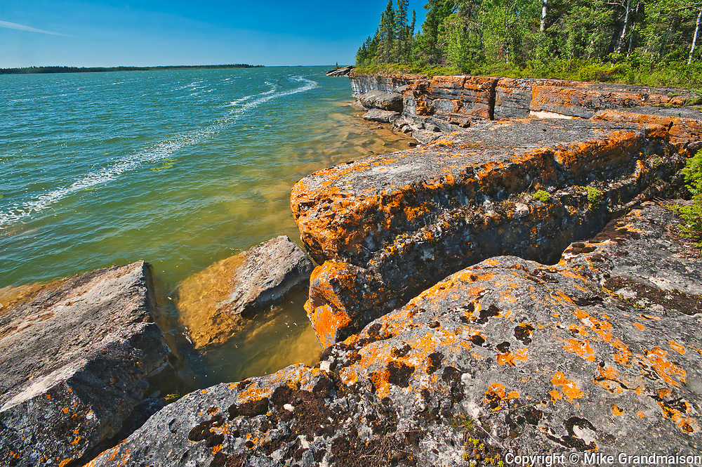 Lichen covered limestone rocks on shore of Rocky Lake<br />