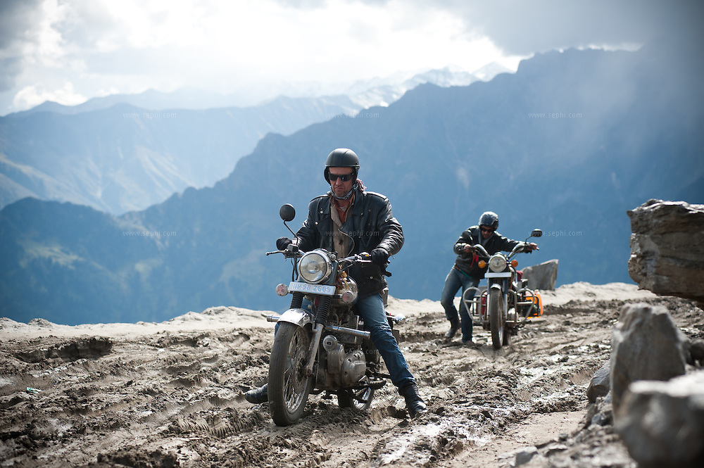Scene from a group of motorcycle riders riding Royal Enfield bikes on a tour from Manali to Spiti in HImachal Pradesh Rohtang Pass at an altitude of 13,051 ft (3,978 m)) is a high mountain pass some 51 km (32 mi) from Manali. It connects the Kullu Valley with the Lahaul and Spiti Valleys of Himachal Pradesh, India.