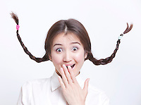 Portrait of surprised young woman with braids curling upwards against white background
