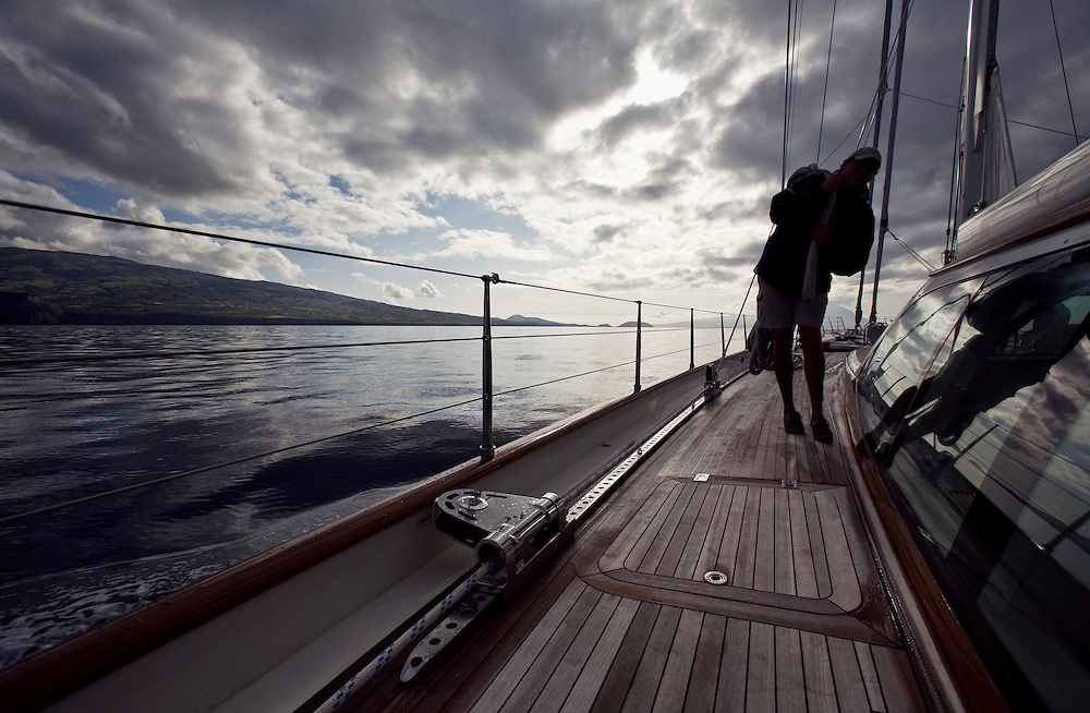 A crew member carries a dock line down the deck as the boat prepares for arrival in the Azores. They will tie to the dock in the harbor of Horta on the island of Faial. One of of the Azores,  a group of islands in the Atlantic that are a part of Portugal and the European Union. .A larg sailing yacht, Scheherazade, arrives at the harbor of Horta on the island of Faial. One of of the Azores, which is a group of islands in the Atlantic that are a part of Portugal and the European Union.