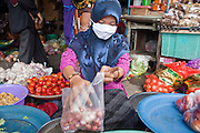 """Sept. 26, 2009 -- YALA, THAILAND: A Muslim market vendor wears a surgical mask because of the pollution in the market in Yala, Thailand. Thailand's three southern most provinces; Yala, Pattani and Narathiwat are often called """"restive"""" and a decades long Muslim insurgency has gained traction recently. Nearly 4,000 people have been killed since 2004. The three southern provinces are under emergency control and there are more than 60,000 Thai military, police and paramilitary militia forces trying to keep the peace battling insurgents who favor car bombs and assassination.  Photo by Jack Kurtz / ZUMA Press"""