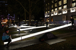 """05/10/2016. Visitors play on 'Impulse', part of the """"Pause and Play"""" series comprising of 15 interactive acoustic, light up see-saws that  illuminate and produce sound when in motion.<br /> London, UK. Photo credit: Ray Tang"""