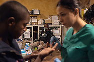 A Baobab's volunteer doctor is examining scabies scars while a migrant having his daily aerosol therapy.