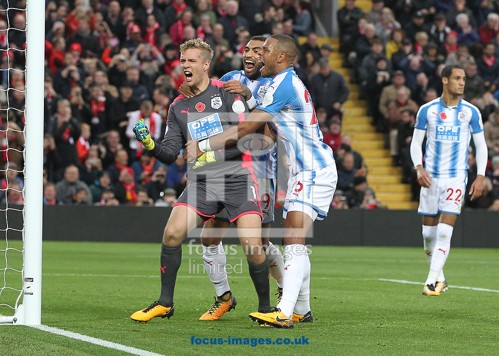 Jonas Lossl of Huddersfield Town celebrates with Daniel Williams and Mathias Jorgensen after saving the penalty attempt by Mohamed Salah of Liverpool during the Premier League match at Anfield, Liverpool.<br /> <br /> Picture by Michael Sedgwick/Focus Images Ltd +44 7900 363072<br /> <br /> 28/10/2017