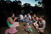 GRUPO DE JOVENES AMIGOS DE NACIONALIDAD ARGENTINA (los varones) Y FRANCESA (las mujeres, Audrey Mandin A LA EXTREMA IZQUIERDA Y Pauline Jolly a la extrema derecha) TOMANDO MATE AL ANOCHECER A ORILLA DEL RIO, EN UNO DE LOS NUMEROSOS CANALES DEL DELTA DEL RIO PARANA, DIQUE LUJAN, PROVINCIA DE BUENOS AIRES, ARGENTINA (PHOTO © MARCO GUOLI - ALL RIGHTS RESERVED)