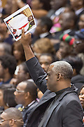 Mourners hold a photo during the funeral service for slain State Senator Clementa Pinckney at the TD Arena June 24, 2015 in Charleston, South Carolina. Pinckney is one of the nine people killed in last weeks Charleston church massacre.