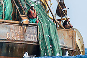Commercial fisher standing at the back of a commercial purse-sein trawler with the trawl nets, Cape Canyon Trawl Grounds, South Africa