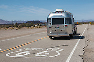 An Airstream Bambi camper trailer is pulled along historic Route 66 near Amboy, California.