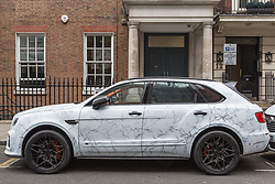 "A ""marble"" £260,000 Ferrari 812 Superfast, capable of 0-60 in 2.9 seconds and £182,000 Bentley Bentayga SUV, also in ""marble"" are seen parked on Stanhope Gate near The Dorchester in Mayfair, having just been flown for their owner to the UK from Dubai. The marble effect is created by ""wrapping"" the car in printed vinyl, and is a popular method of changing the look of a car without having to have it repainted. London, August 02 2019."