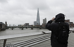 © Licensed to London News Pictures. 29/05/2015. London, UK. A man on the Millennium Bridge takes a photograph along the River Thames during wet and overcast weather in London today. Today is the first day of British Summer Time (BST).  Photo credit : Vickie Flores/LNP