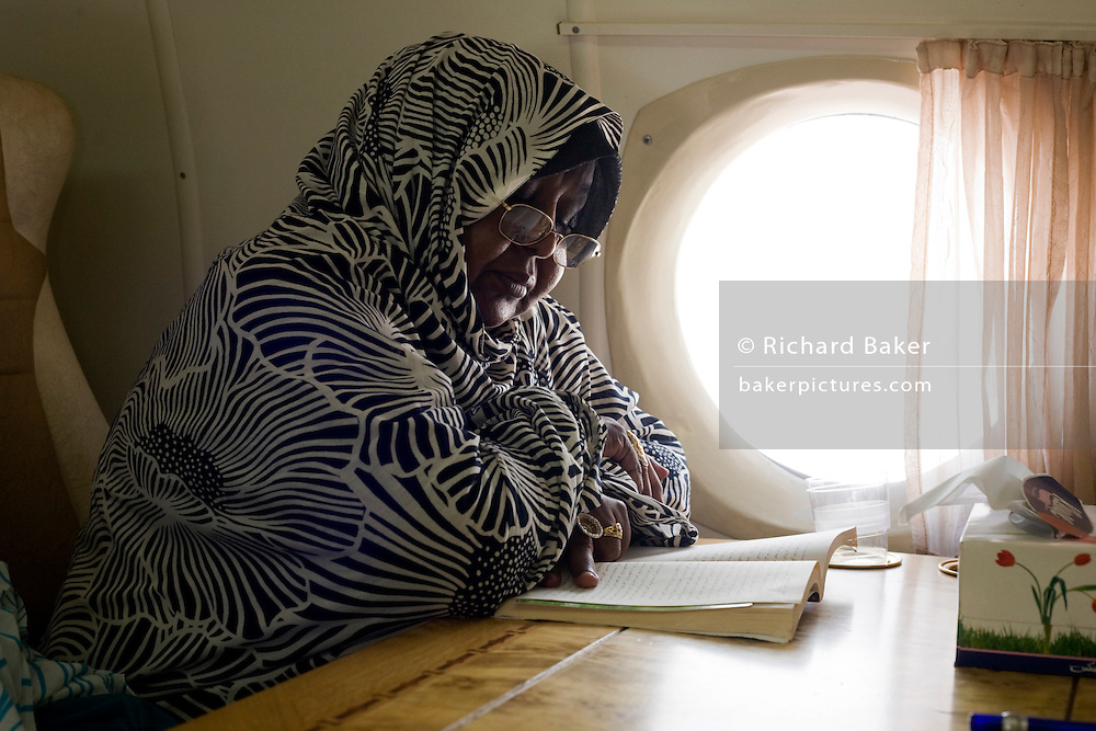 Seated by the window of a chartered Russian Antonov aircraft during flight to Al Fasher (also spelled, Al-Fashir), Dr Mazahir Mohammed reads a book on the return journey of a the first-ever international Conference on Womens' Challenge in Darfur, swhere women from remote parts of Sudan gathereed to discuss peace and political issues. The short flight saves her a hazardous five-day drive by road, known for extreme acts of violence by rebels and Janjaweed soldiers.