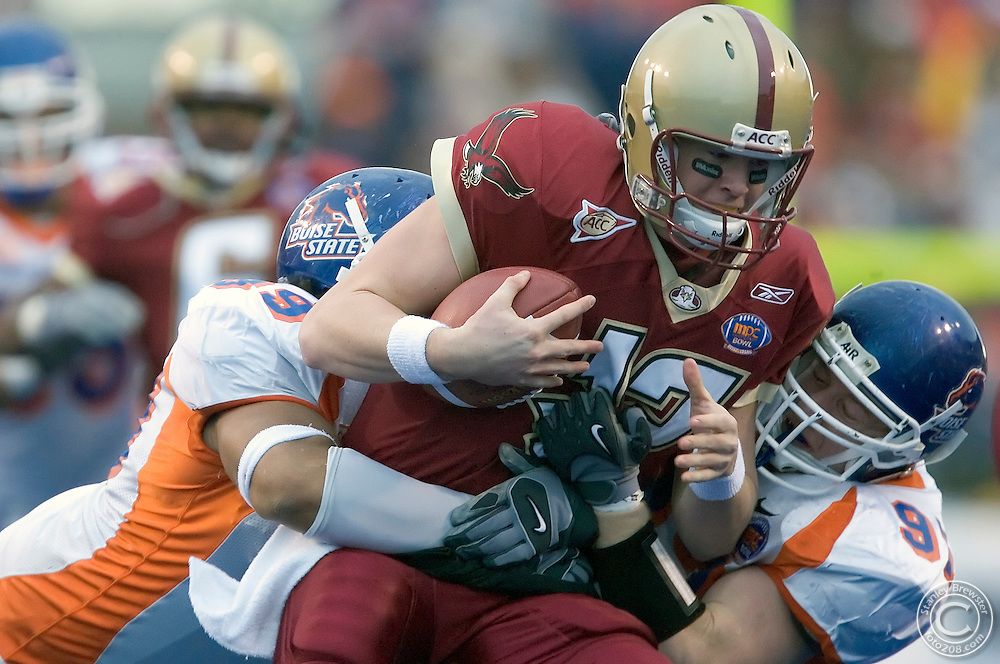 12-28-05-Boise ID. Boise State vs. Boston College in the 2005 MPC Computers Bowl in Bronco Stadium. Alex Guerrero (L) sacks BC quarterback Matt Ryan (C) with the help of Nick Schlekeway (R). The Eagles beat the Broncos 27-21.