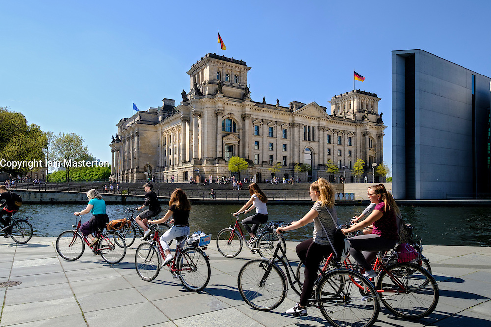 View of the Reichstag Parliament building and tourists on bicycles beside  River Spree in Berlin Germany