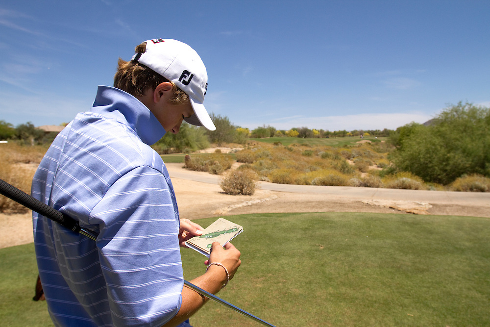 American Junior Golf Association player Jordan Spieth consults his yardage book at the Thunderbird International Junior tournament where there are no caddies.
