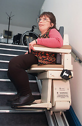 Woman with disability using stair lift,