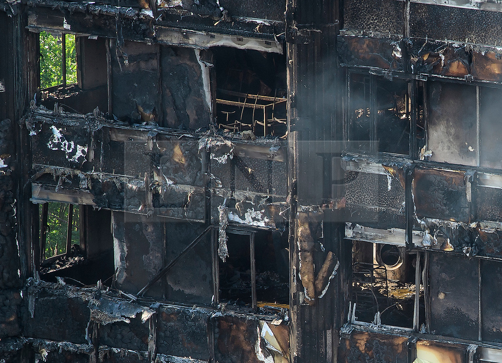 © Licensed to London News Pictures. 15/06/2017. London, UK. What appears to be a washing machine and a table and chairs. The burnt out remains of the inside of some of the apartments can be seen the Grenfell tower block in west London. The blaze engulfed the 27-storey building with hundreds of firefighters attending the scene. Photo credit: Ben Cawthra/LNP