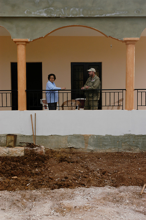 A community liason officer from Mines Advisory Group (MAG) speaking with Soukna Olaïck who discovered a cluster sub-munition in the garden of her home which she is rebuilding after the 2006 Hezbollah - Israel conflict. The village, near the border with Israel was severely contaminated with cluster sub-munitions..Yohmour, Lebanon. 27/11/2008.Photo © J.B. Russell