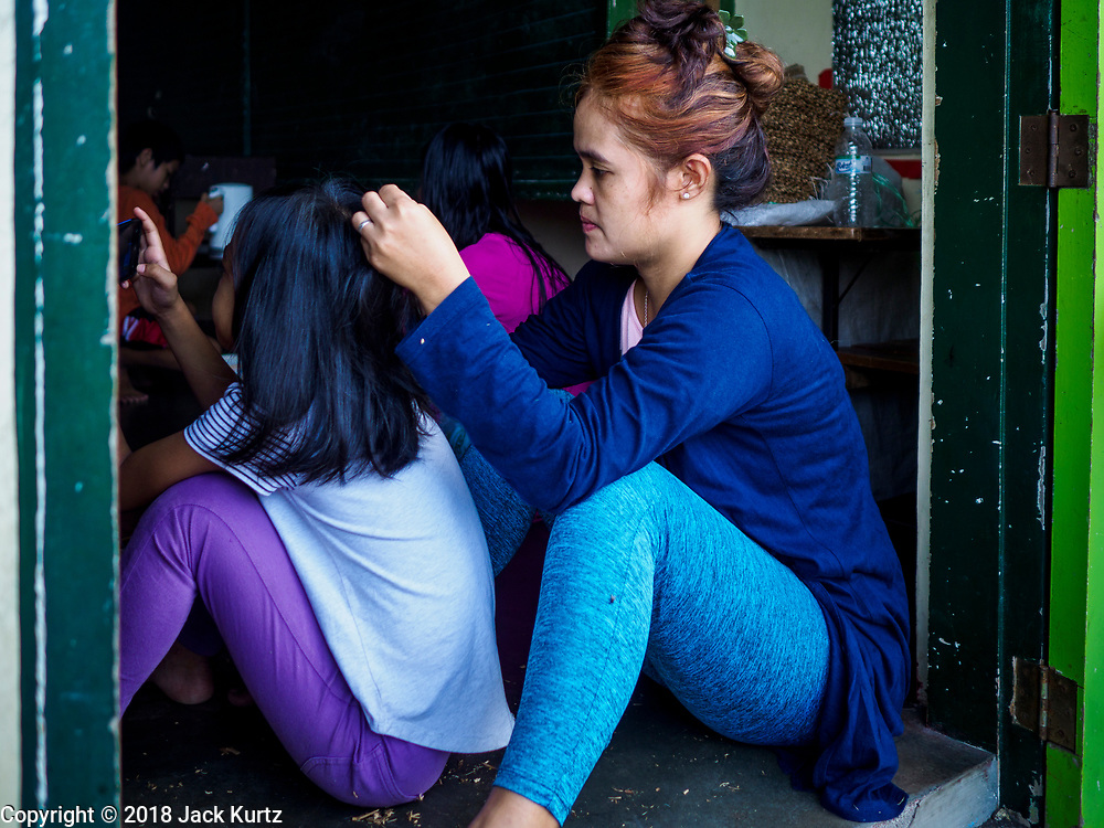 20 JANUARY 2018 - CAMALIG, ALBAY, PHILIPPINES: Teresita Nacor does the hair of her daughter Kristine in an evacuation shelter. More than 30,000 people have been evacuated from communities on the near the Mayon volcano in Albay province in the Philippines. Most of the evacuees are staying at school in communities outside of the evacuation zone.   PHOTO BY JACK KURTZ