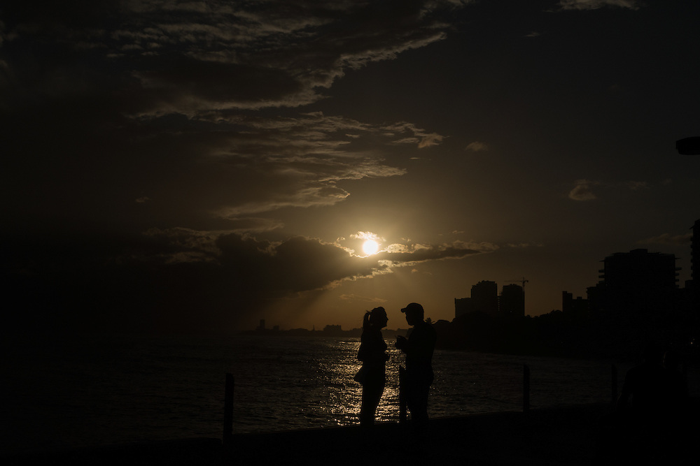 SANTO DOMINGO, DOMINICAN REPUBLIC-DECEMBER 2, 2014: A couple enjoys the view of the ocean  in a park in Santo Domingo's Malecon at sundown. Story on tourism to the Caribbean Island.  (Photo by Angel Valentin/Getty Images for Der Spiegel)