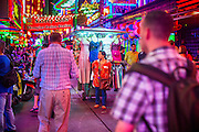 "12 JANUARY 2013 - BANGKOK, THAILAND:  A woman who sells dresses and makeup to the workers in the Soi Cowboy red light district pulls her cart through a throng of tourists on Soi Cowboy in Bangkok. Prostitution in Thailand is illegal, although in practice it is tolerated and partly regulated. Prostitution is practiced openly throughout the country. The number of prostitutes is difficult to determine, estimates vary widely. Since the Vietnam War, Thailand has gained international notoriety among travelers from many countries as a sex tourism destination. One estimate published in 2003 placed the trade at US$ 4.3 billion per year or about three percent of the Thai economy. It has been suggested that at least 10% of tourist dollars may be spent on the sex trade. According to a 2001 report by the World Health Organisation: ""There are between 150,000 and 200,000 sex workers (in Thailand).""    PHOTO BY JACK KURTZ"